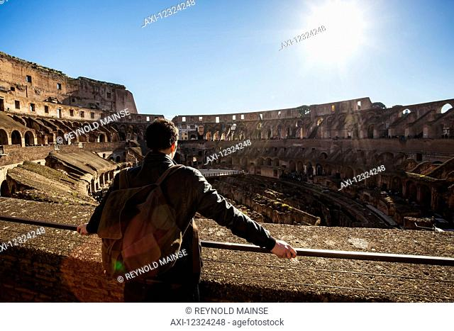 A male tourist stands looking at the Colosseum; Rome, Italy