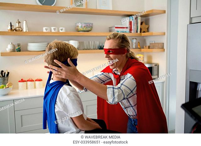 Mother and son pretending to be superhero in the kitchen