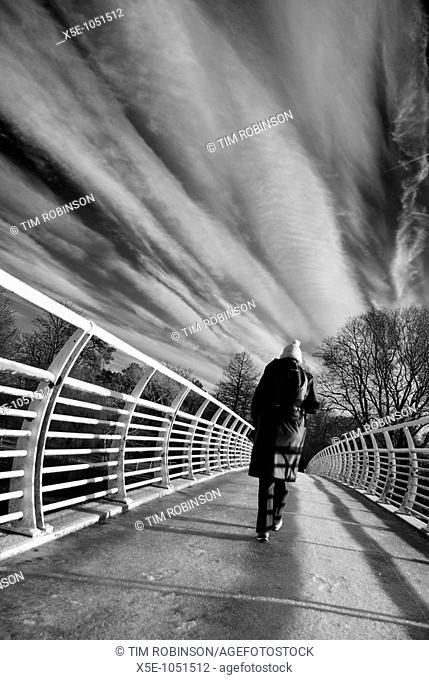 Rearview woman walking over bridge, monochrome