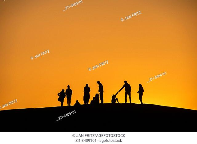 sanddunes with silhouettes of tourists in sunset in desert of Morocco
