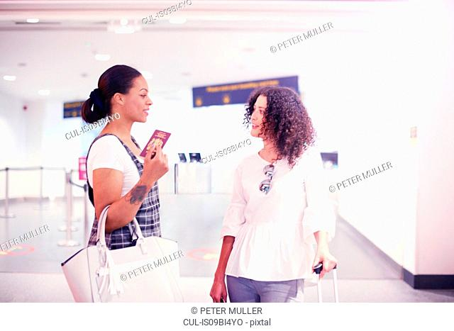 Two women at airport holding passport and luggage