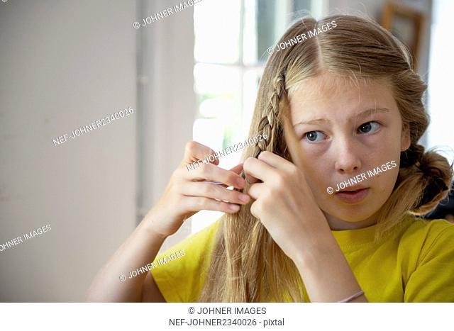 Girl braiding her hair