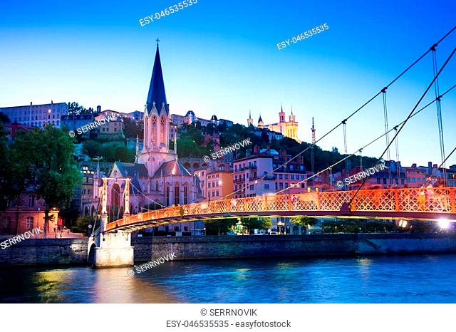 Vieux Lyon, illuminated Saint-Georges church and Passerelle Paul Couturier footbridge on the river Saone at night