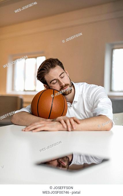 Portrait of young freelancer with basketball having a break