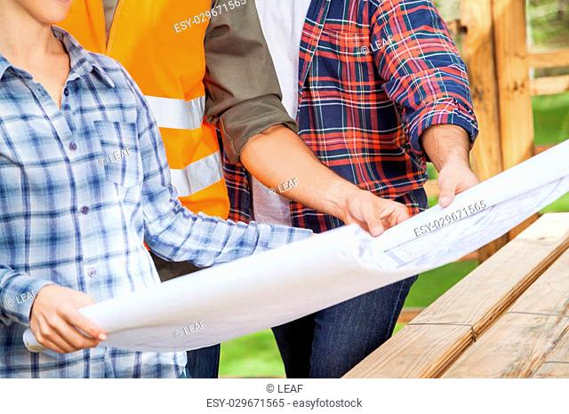 Midsection of male and female carpenters holding blueprint at site