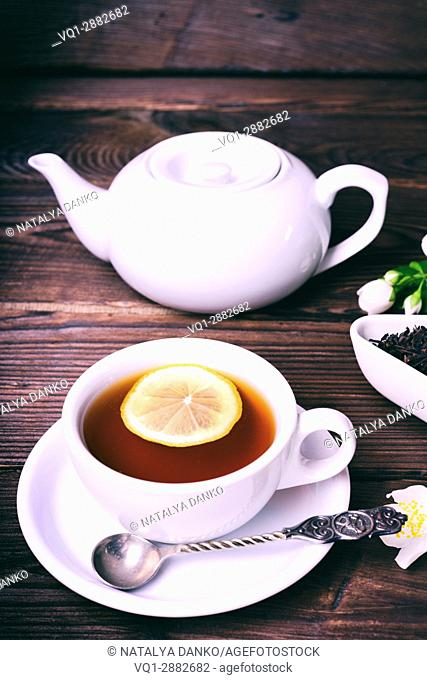 Cup of tea with lemon on a brown wooden background, vintage toning