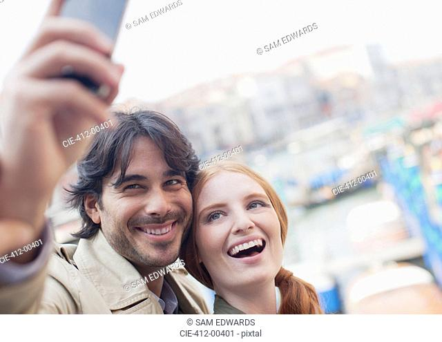 Smiling couple taking self-portrait with cell phone