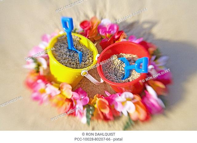 Two sets of brightly colored shovel and pails surrounded by a lei on a sandy beach