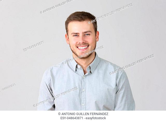Front portrait of a happy man isolated on a grey background