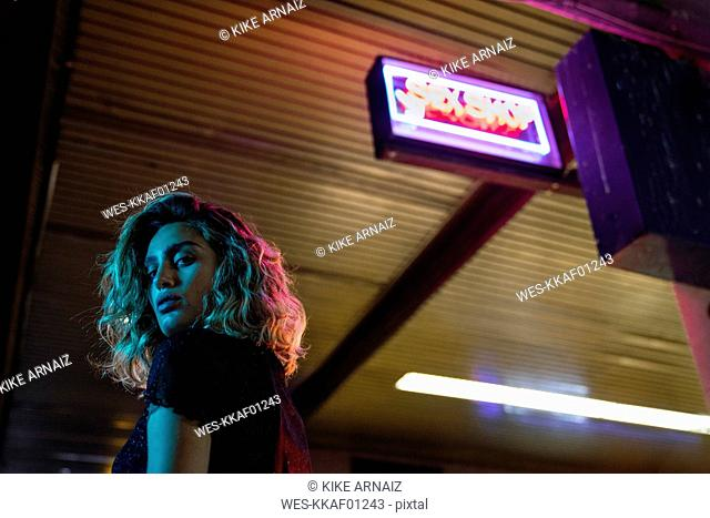 Stylish young woman at night, standing in front of sex shop