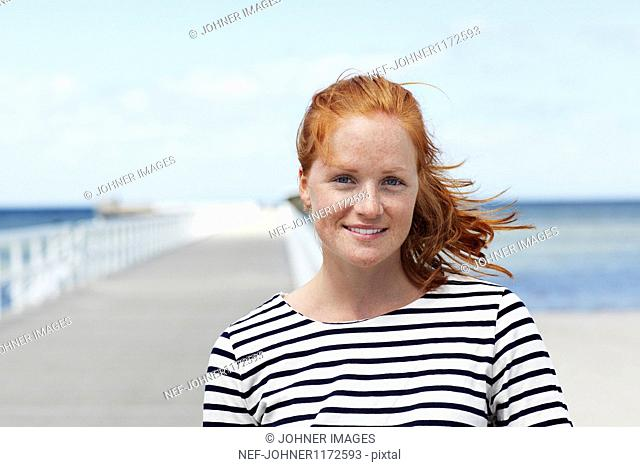 Portrait of smiling redhead woman standing at jetty