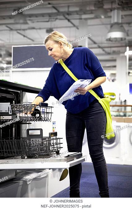 Woman looking at dishwasher in shop
