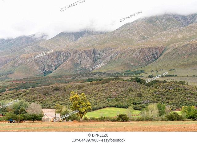 A farm landscape near Matjiesrivier with a waterfall in the back on the slopes of the cloud covered Swartberg (black mountain)