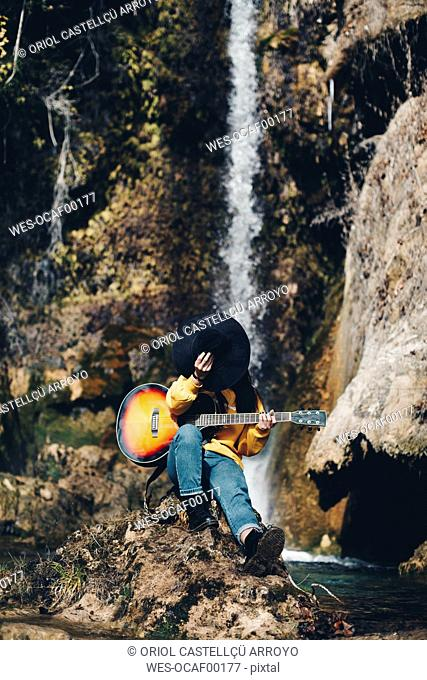 Spain, Lleida, young woman with guitar sitting on rock in front of waterfall covering face with hat