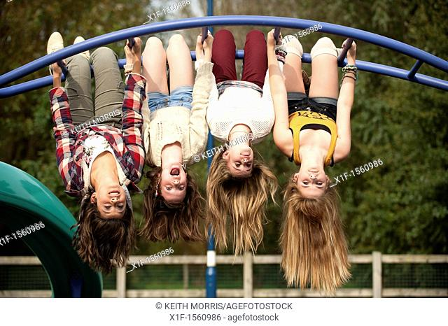 A group of 13 year old teenage girls having fun hanging upside down in a playground UK