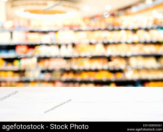White wooden board empty table in front of blurred background. Perspective white wood board over blurred colorful supermarket products on shelvest - mockup for...