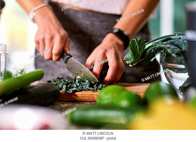 Hands of young woman slicing cabbage at kitchen table