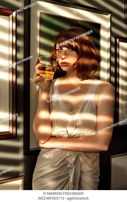 Woman having a drink in a shadowed room