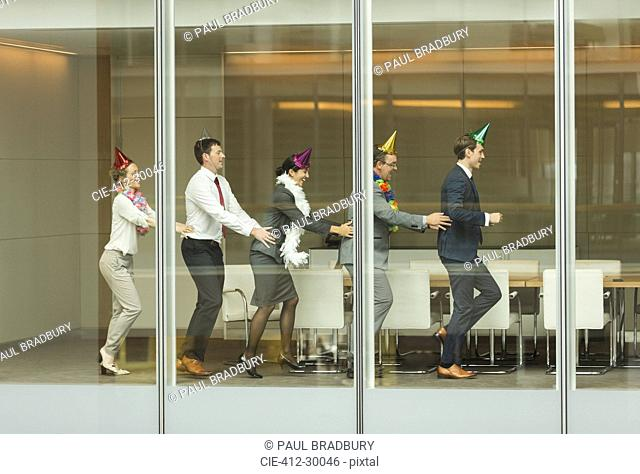 Business people wearing party hats dancing in conga line at conference room window