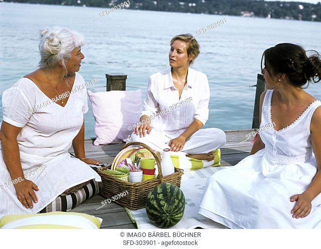 Three women sitting around picnic basket on landing stage