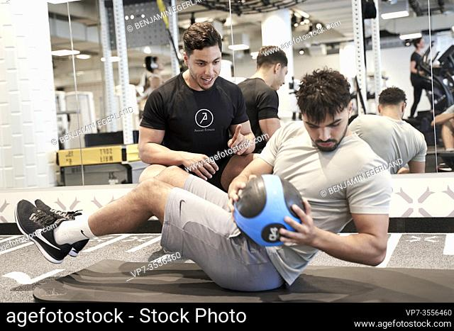 Personal trainer assisting man exercising in gym