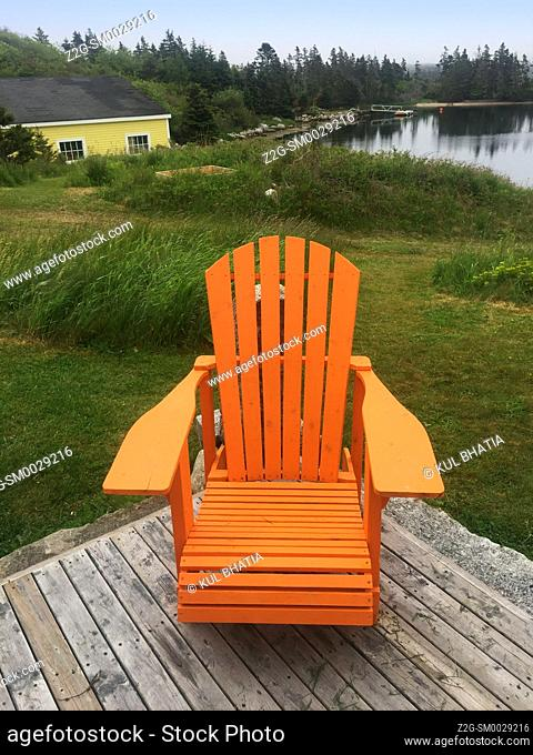 An empty adirondack chair on a deck overlooking the water, a tranquil spot, Nova Scotia, Canada