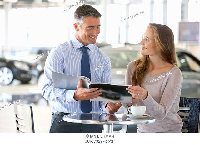 Salesman and customer looking at brochure at table in car dealership showroom