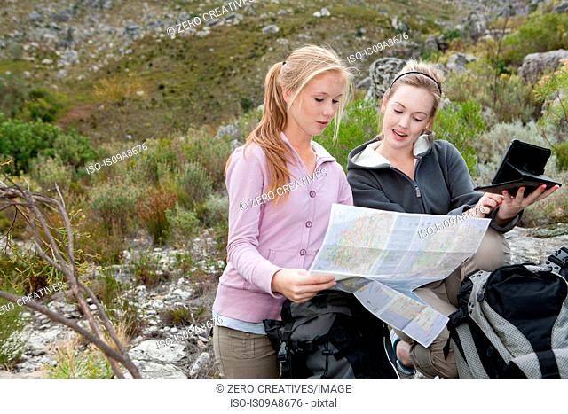 Two young female hikers looking at map