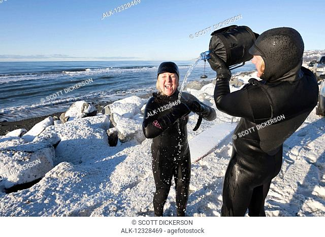 Female surfer rinsing off along Homer Spit Beach in winter, South-central Alaska; Homer Spit, Alaska, United States of America
