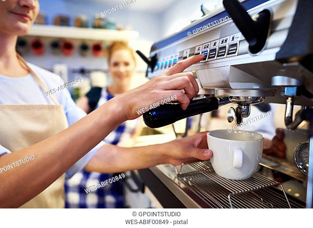 Female barista making coffee at a cafe