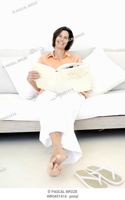 Portrait of a mature woman sitting on a couch and holding a photo album