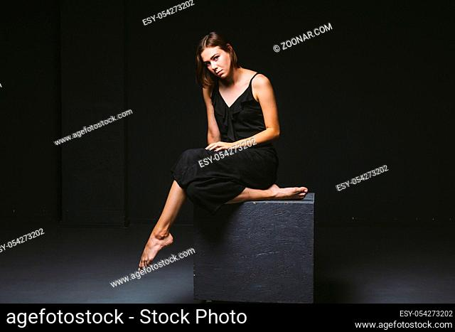 Young Caucasian female model posing in studio black background.Girl sitting in a black dress on a dark wall. Subject severe poor psychological state, intra