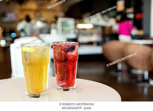 Mixed berry sparkling tea and green mint tea on table in coffee shop