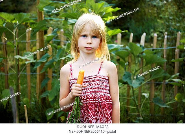 Portrait of girl holding carrot