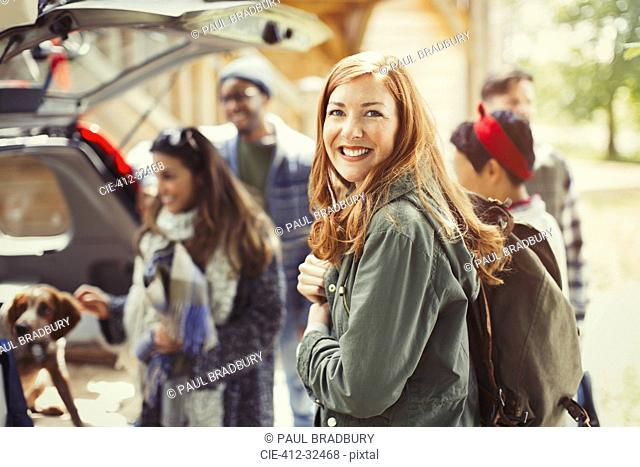 Portrait smiling hiker holding backpack with friends at back of car