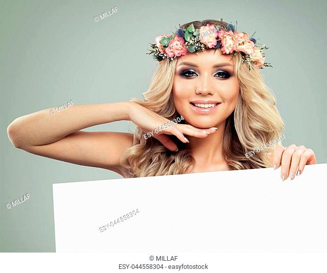 Happy Young Woman with Flowers Hairstyle Holding White Banner for Text. Blonde Beauty. Fashion Model with Long Permed Curly Hair and Perfect Makeup