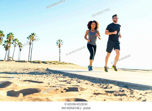 Couple running on pathway at beach, low angle view