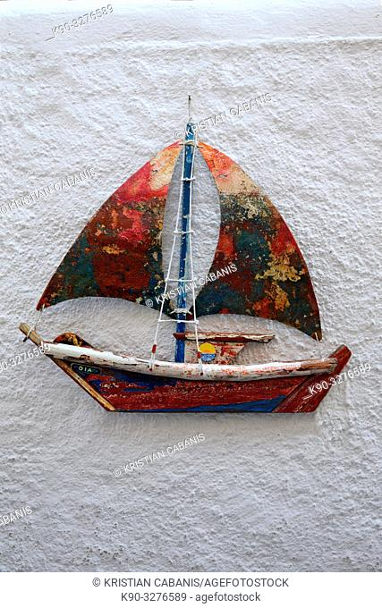 Toy sailboat hanging on a white wall, Oia, Santorin, Greece, Europe