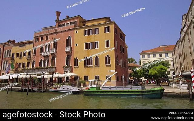 Tracking moving shot along the Grand Canal near the station showing Venetian Palaces, Venice, Italy