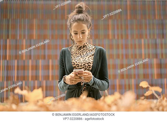fashionable woman using smart phone, typing text message, in front of geometrical pattern, lines, autumn season, in Munich, Germany