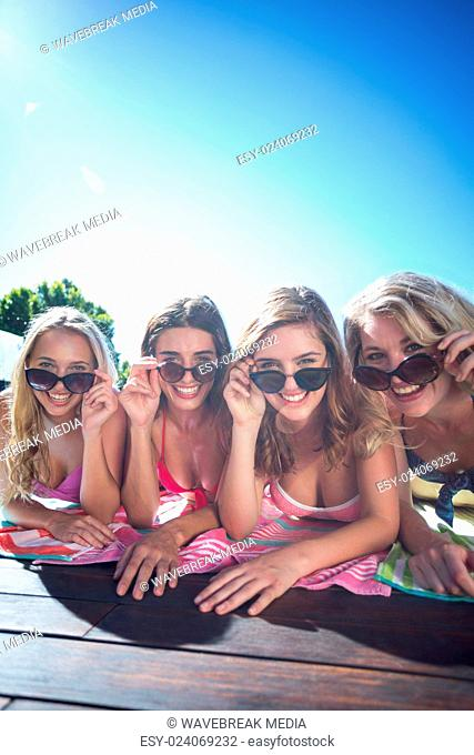 Group of happy friends lying near pool