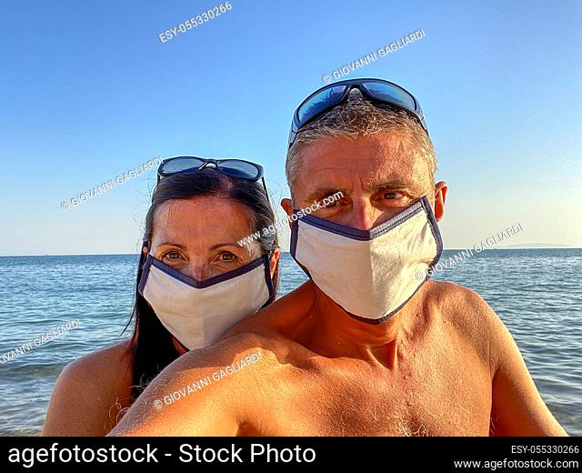 Man and woman taking selfie on the beach wearing masks in covid time