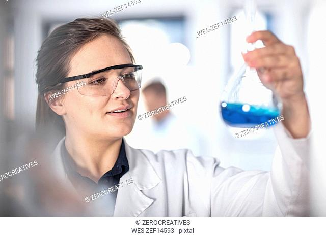 Scientist working in lab looking at flask