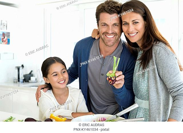 Couple with their daughter enjoying in the kitchen