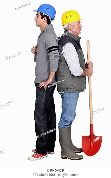 duo of manual workers standing back to back