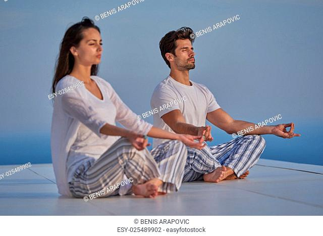 young couple practicing yoga at sunset in modern home terace with ocean and sunset in background