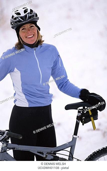 Woman holding bicycle in snow