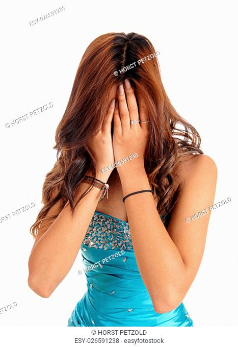 A young woman in a blue evening dress covering her face, she is ashamed.in closeup, isolated for white background.