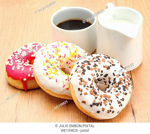 donuts coffee and milk on wooden board