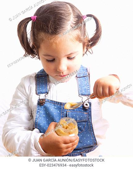 Portrait of happy girl eating a fruit jar of baby food. Isolated over white background